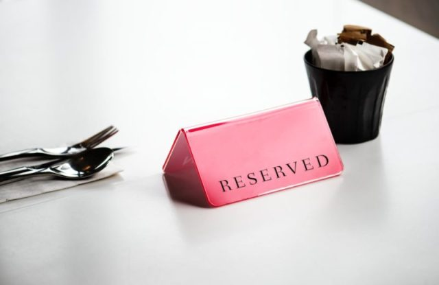 red reserved signage beside stainless steel spoon and fork on white surface