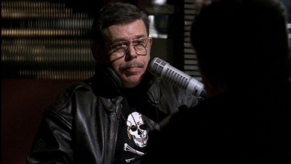 Art Bell poses for a photograph in-front of a microphone.