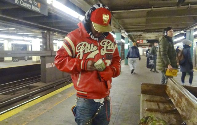 """Meet Jihad or """"J,"""" who we spotted at Hoyt-Schermerhorn waiting for the A train. He had on a red jacket, chain, gloves, shoes and made a point to pull out a red cell phone. He was certainly matching. He says he produces music."""