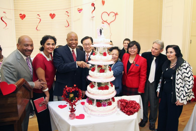 Brooklyn Borough President Eric Adams cuts a wedding cake, donated by Mr. and Mrs. Timmy Moy (center), during his Sweethearts celebration in honor of Valentine's Day at Borough Hall; he is also joined by (from left to right) HealthFirst Vice President of External Affairs George Hulse, Deputy Brooklyn Borough President Diana Reyna and Honorary Chinese Ambassador to Borough Hall Winnie Greco, in addition to couples married for 50 years or more.