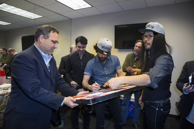 Barclays Center's SVP of Programming, Sean Saadeh, and Director of Booking, Tyler Bates, present the Avett Brothers with Brooklyn Nets hats and custom jerseys before the band took the stage in Brooklyn on Friday, March 7. Photo: Angela Cranford/Barclays Center