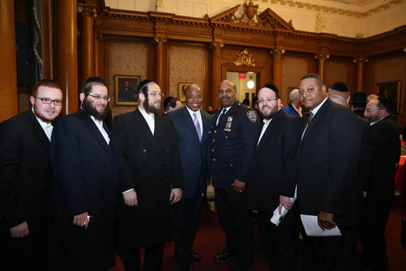 Brooklyn Borough President Eric Adams joins (from left to right) community activist Yanky Eisdorfer, Administration for Children's Services representative Pinny Ringel, executive director of JCC of Greater Williamsburg Rabbi Moshe Indig, 88th Precinct commanding officer Deputy Inspector Scott Henderson, special assistant to Borough President Adams Joel Eisdorfer and Patrol Borough Brooklyn North Lieutenant Marvin Luis at a pre-Passover community open dialogue in the courtroom of Borough Hall. Photo: Yossi Goldberger