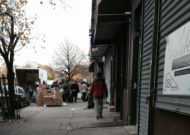 Volunteers load boxes of food and people line up down the block to receive donated food items at the Bed-Stuy Campaign Against Hunger