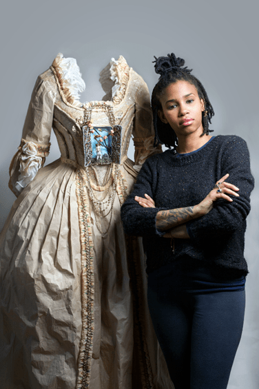 """Artist Fabiola Jean Louis stands next to the paper sculpture used in the portrait, """"Madame Leroy"""" Photo: www.broadwayworld.com"""