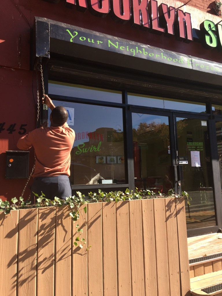 Jean Alerte, owner of Brooklyn Swirl, pulls down the store's gate for the final time this year.