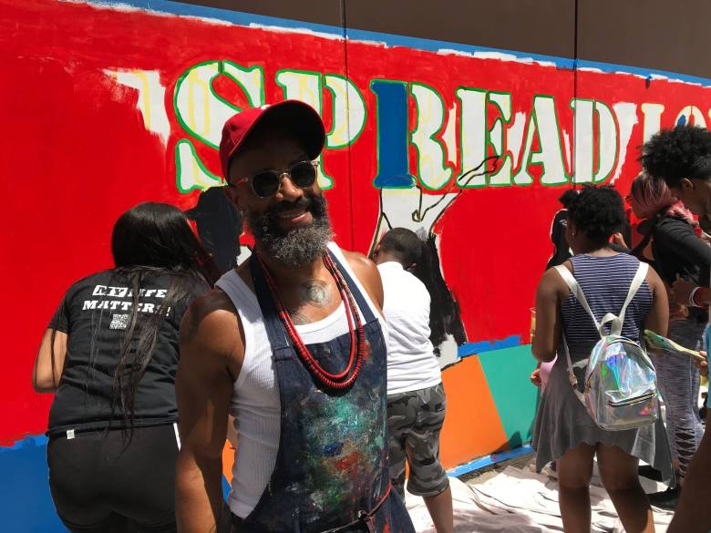 """Patrick Dougher stands in front of the """"Spread Love"""" mural"""