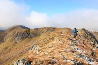 Peter Evans walks along the ridge towards Stob a' Choire Dhomhain with Carn Eighe to the left.