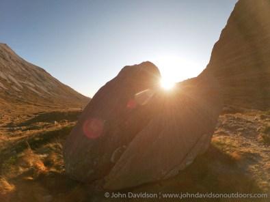 The sun rises through a split boulder alongside the Coire Dubh Mor path.