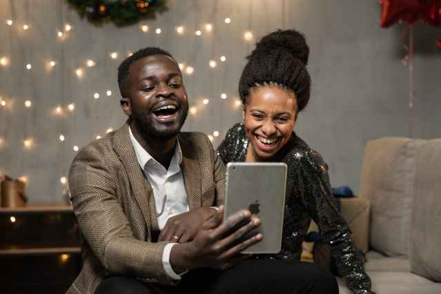 two black people looking at an iPad smiling