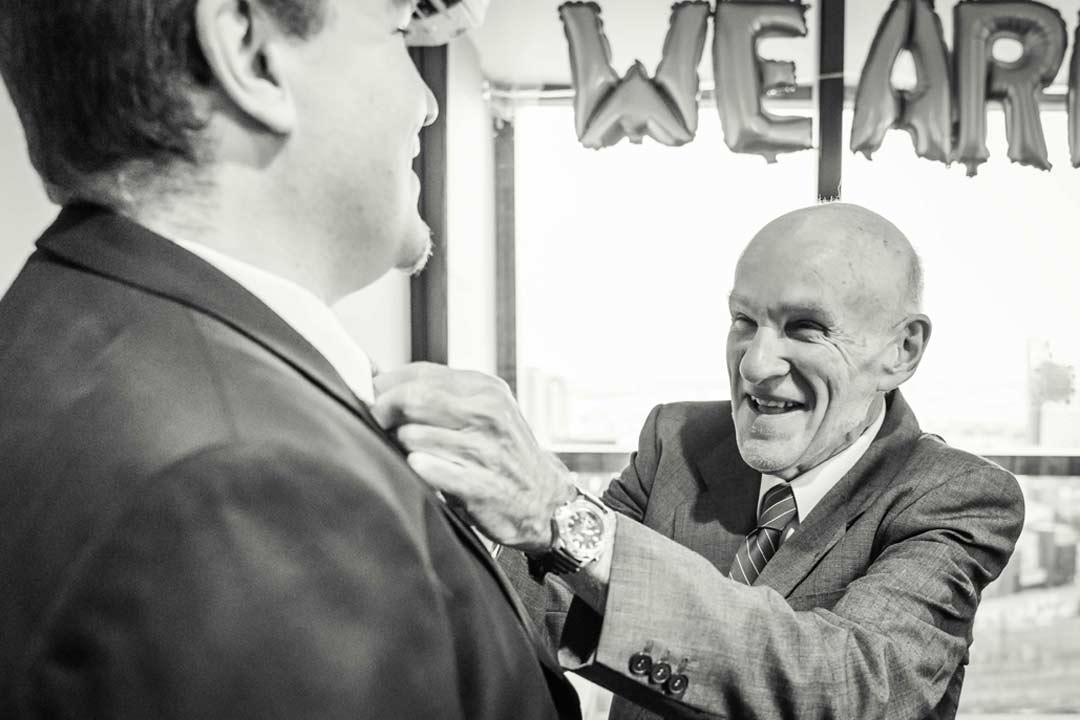 emotional image of father helping son put his tie on captured by wedding photographer Black Avenue Productions in Dockland Melbourne