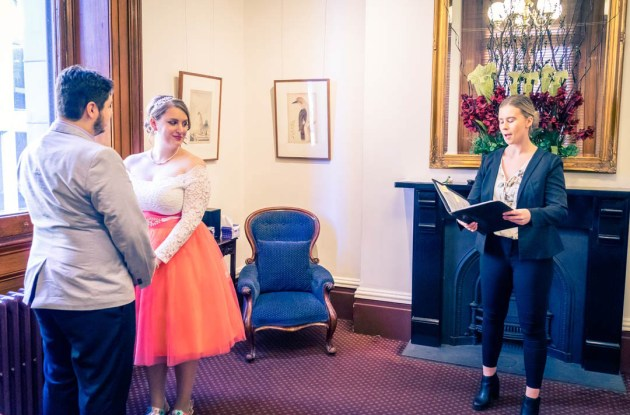 candid moment of wedding ceremony with civil celebrant reading vow in Victorian Marriage Registry in Old Treasury Building