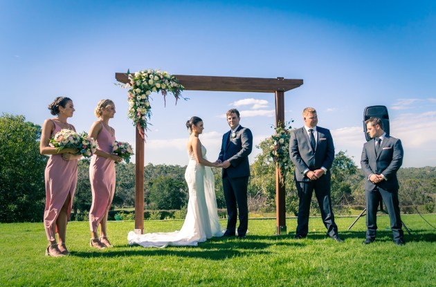trendy outdoor rustic boho barn wedding ceremony moment with bride and groom holding hands