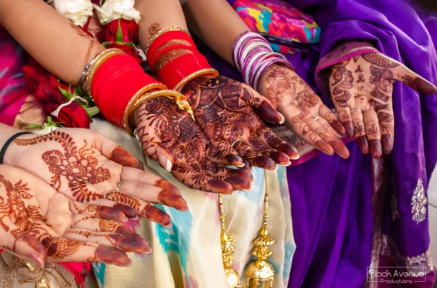 bridal party and bride showing off hand henna tattooed on their wedding day in Hindu Temple