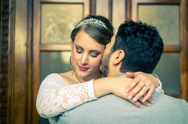 fairy tale bride hugged husband romantically outside parliament house Melbourne in her lace bridal dress
