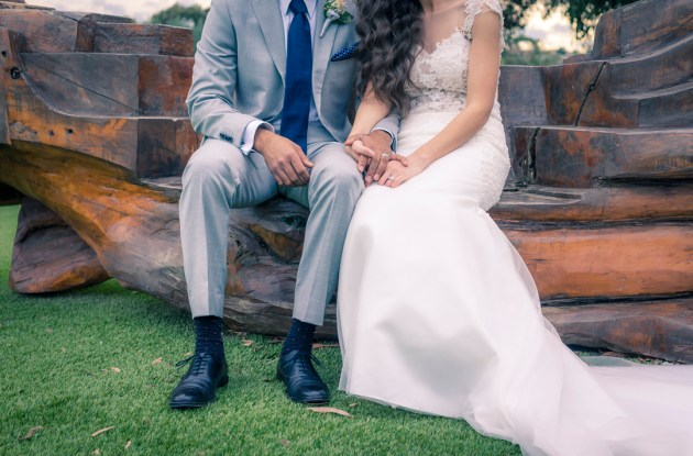 wedding photo showing bride groom holding hands sitting on wooden bench near yarra river VIC Australia