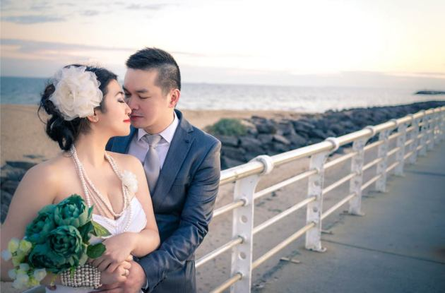 Melbourne wedding photography showing bride and groom happily look at each other on St Kilda pier Australia