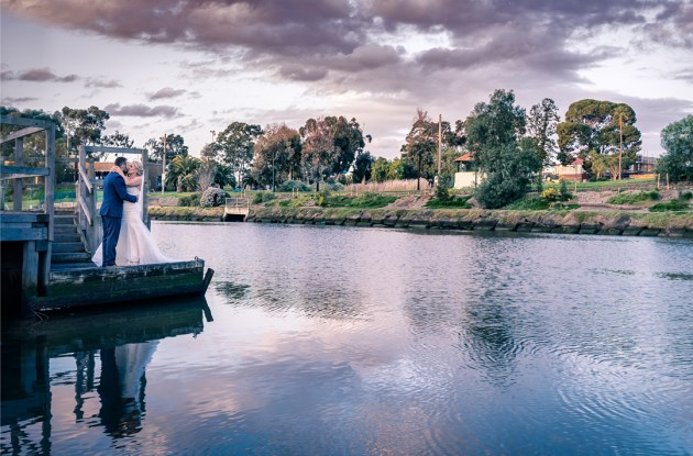 romantic wedding picture of bride and groom standing at jetty with yarra river background during sunset magic hour