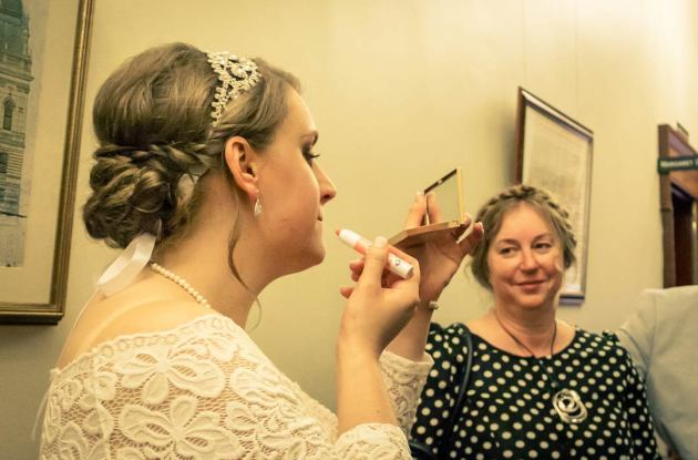 bride put lipstick on in front of her mom capture by candid wedding photographer Black Avenue Productions