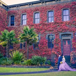 newly engaged boyfriend girlfriend posing outside red leave wall of Victoria Barracks during autumn fall for their pre wedding photo