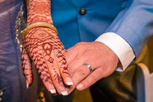 Melbourne wedding photographers captured the moment of henna tattooed brides hand holding to grooms hand, showing their wedding rings