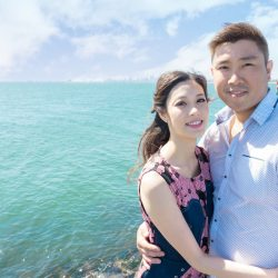 four season engagement photo of young Hong Kong couple standing in front of blue ocean in sunny day