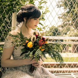 woodland theme wedding bride holding a greenery forest style bright flower sitting at Overnewton Castle wedding reception Melbourne