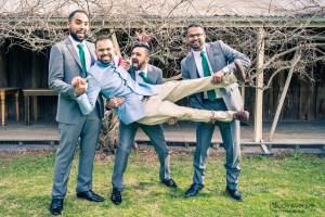cheeky groomsmen holding groom up to pose for wedding photo outside a warehouse at Baxter Barn 2017