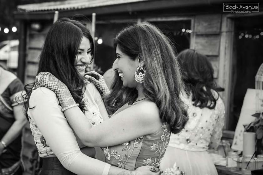 emotional black and white image showing two best friends hugging celebrating a rustic greenery barn warehouse wedding capture by Black Avenue Productions