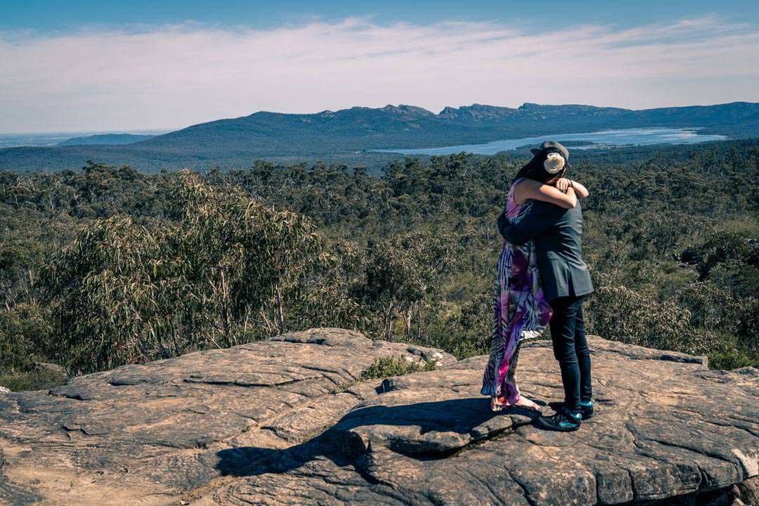 happy newly engaged couple hugged for a long time at Reeds look out the Grampians in Australia during their surprise proposal photography by Black Avenue Productions