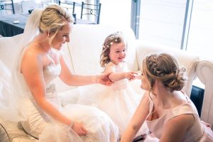 candid moment of bride and sister and flower girl having fun in the morning