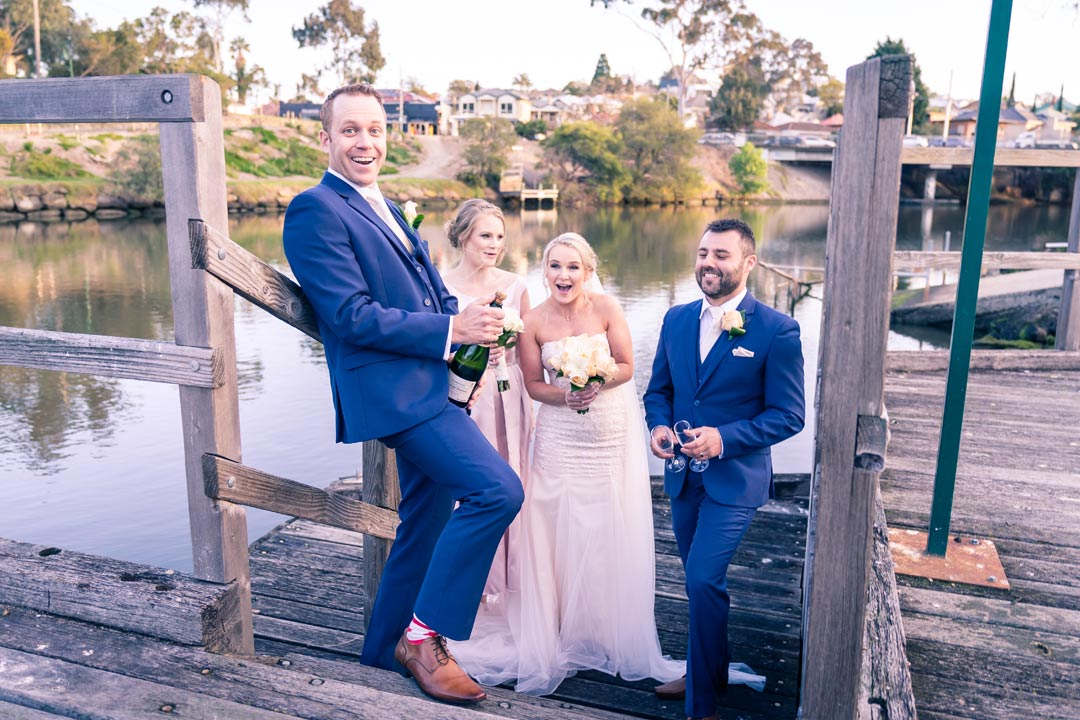 candid photo of bridal party opening champaign by the Yarra river before reception