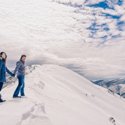 award winning image of engaged couple climbing up the top of a snow mountain in Falls Creek Victoria Australia by Black Avenue Productions
