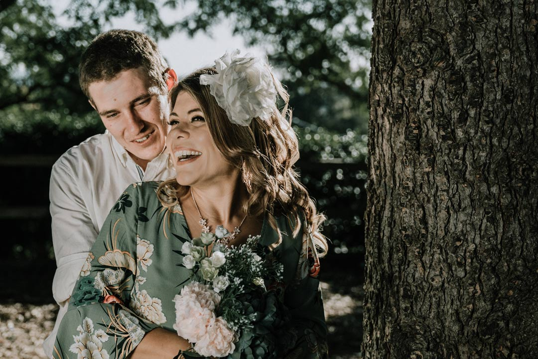 wedding photo of laughing smiling bride groom holding green lily bouquet happily ever after