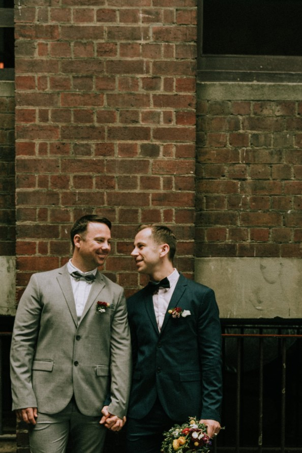 same sex couple happily laughing in front of a brick wall at Hardware Lane wedding photo