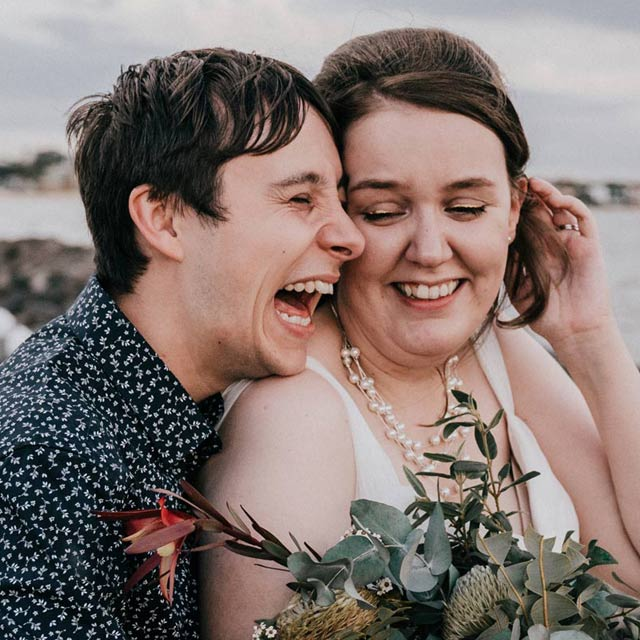 happy wedding photo showing couple laughing in front of Little Blue restaurant on St Kilda Pier by Melbourne wedding photographers Black Avenue Productions