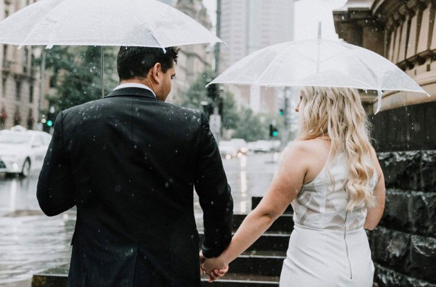 husband wife walking in the rain on their rainy day wedding 2018 at Old Treasury Building Melbourne on Spring Street