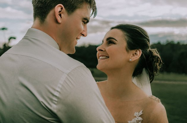 candid wedding photography moment of just married bride and groom look at each other full of love