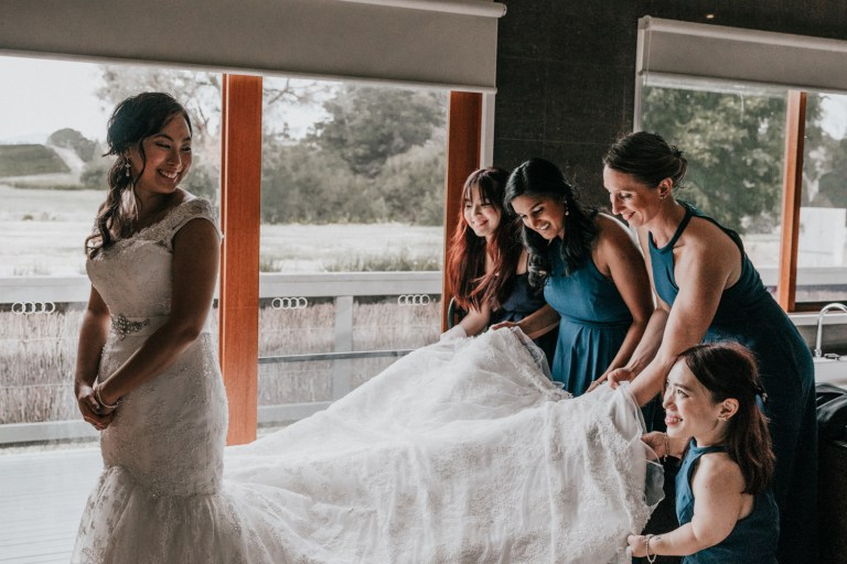 bridesmaids in teal bridesmaid dress helping bride with her lace vintage floor length bridal dress with chapel train