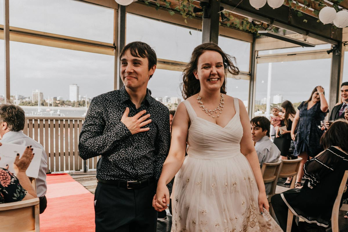 Just married husband and wife walked down the aisle together feeling grateful and joy at Little Blue Kiosk in St Kilda Pier Melbourne captured by candid wedding photographers and videographers team Black Avenue Productions