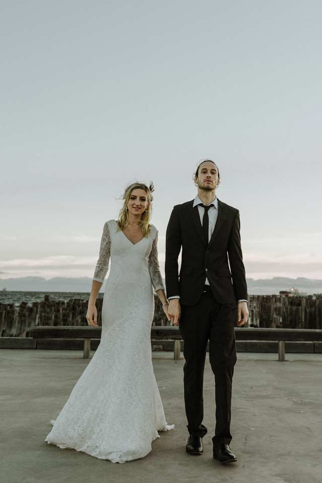 boho bride and trendy hot groom holding hands on Princess pier during sunset hour by Black Avenue Productions