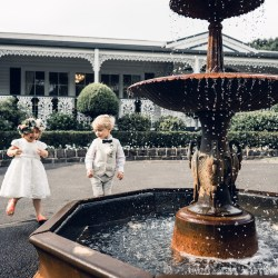 flower girl play at the fountain at Ballara receptions wedding venue in Eltham Melbourne