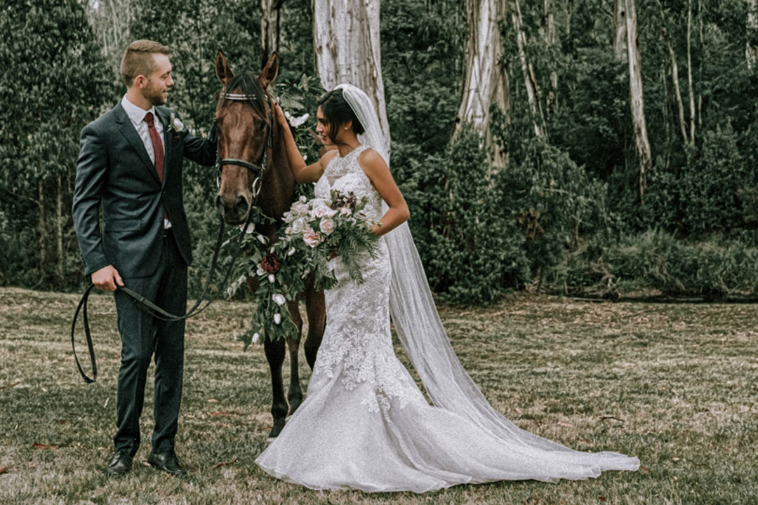 husband and wife newly wedded couple walking with pet horse at rustic farm wedding Melbourne