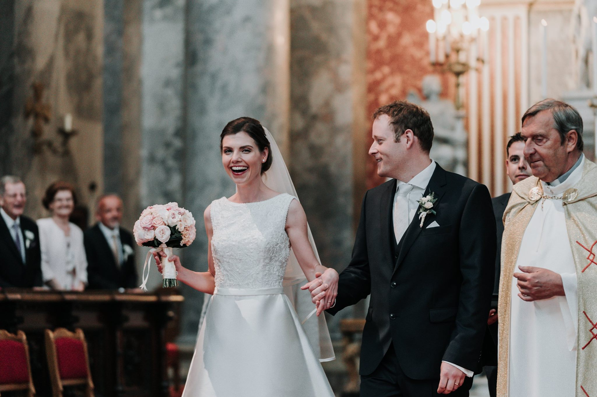 happy bride laughing after her wedding ceremony in the biggest church in Hungary, honest moment captured by photographed by award winning photographer Derek Chan from Black Avenue Productions