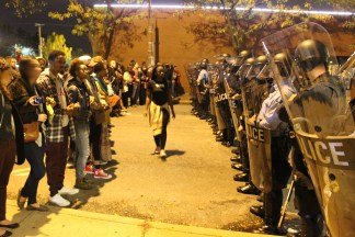 """Protesters stand in front of police line chanting """"It is a fight for our freedom. It is our duty to win. We must love and support each other. We have nothing to loss but our chains."""" Photo credit: Briana Simmons"""