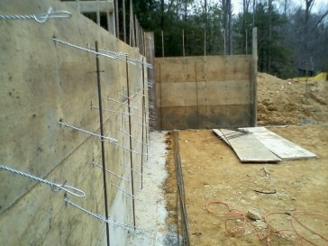 The metal holds the two pieces together so concrete can be poured in the middle. The loops in the metal is where rebar slides in to provide support