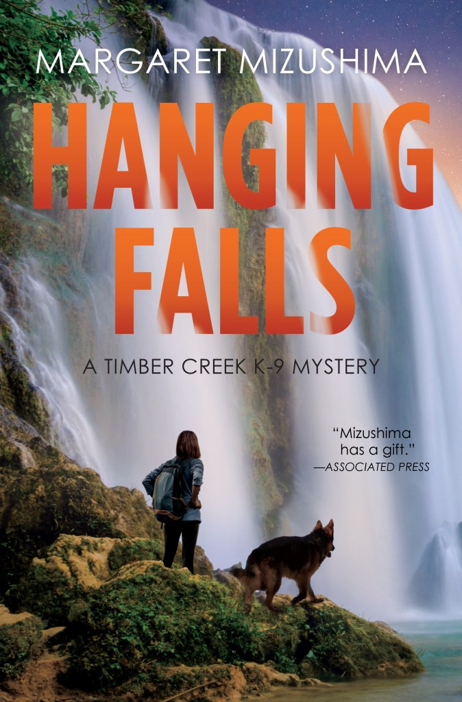 Book Cover. Hanging Falls by Margaret Mizushima. A Timber Creek K-9 Mystery. Dog and person in front of a waterfall.