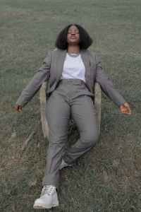 trendy african american lady relaxing on armchair on grassy field
