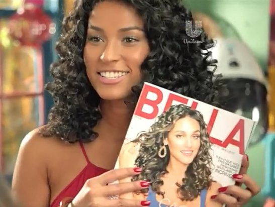 Actress displays magazine featuring Débora Nascimento on the cover