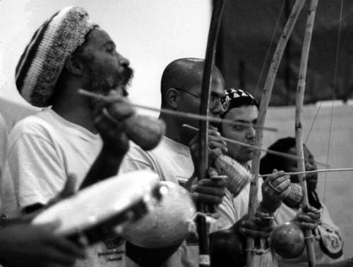 Capoeiristas playing berimbaus