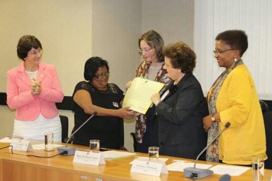 Ministers Maria do Rosário, Eleonora Menicucci and Luiza Bairros present Maria de Lourdes Pimentel with a certificate acknowledging Brazil's responsibility in her daughter's death